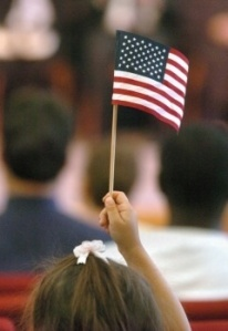 A child holds up an American flag during the U.S. citizen naturalization ceremony at the Gerald R. Ford Museum (Mark Copier | The Grand Rapids Press)