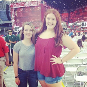 """Sophomore Madeline Skiles (Right) and friend pose at their seats next to the stage where One Direction performed. Skiles and friend joined over 100,000 fans (AKA """"Directioners"""") as they experienced the night of their dreams."""