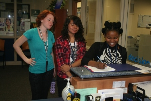 Shukrani Nsenga, Stephanie Gonzalez, and Arya Malmgren sign up for on-site admissions. It is an exciting yet stressful time of year for these students. Photo Credit / Caitlin Commissaris