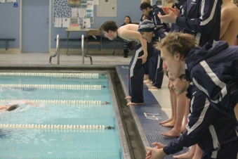 Swimmer Thaddeus Pollard cheers on for his fellow teammates in a meet. The swim team looks to make big waves in the SMAC conference this year. Photo Credit: Yearbook