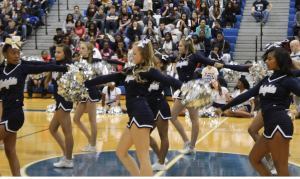 The varsity cheerleaders perform the pom pass during their pep rally routine. The pom pass took the cheerleaders hours to perfect. Photo Credit / Jordan Brown