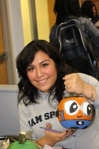 Senior Leslie Julian is painting a cheerful pumpkin in order to brighten up someones day. Photo Credit: Jonathan Lo