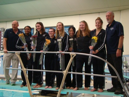Swim team coaches pose with their senior swimmers. Coach Mahar, Makayla Langford, Isabelle Tavares, Lily Krone, Aude Kuzniak, Megan Youngs, Melissa Commissaris, and Coach Digget stand on the diving board. Photo Credit / Caitlin Commissaris