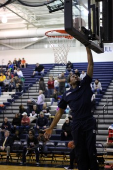 Senior DQ Wiggins goes for a layup during warm ups. With his efforts the Knights were able to defeat the Blue Devils 60 to 25. Photo Credit / Chris Hybels
