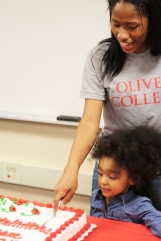 "Tizhane Mitchell cuts into her Olivet cake with her younger sister at her side. ""My sister is my motivation, I did it for her,"" says Mitchell. Photo Credit / Caitlin Commissaris"