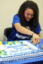 Haven Johnston makes the fist cut in her Muskegon Community College cake. She gladly hands out slices to her high school friends. Photo Credit / Caitlin Commissaris