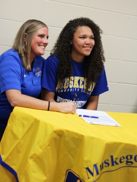 Haven Johnston smiles happily about her commitment to Muskegon Community College. The basketball coach for MCC stays by her side for reassurance. Photo Credit / Caitlin Commissaris