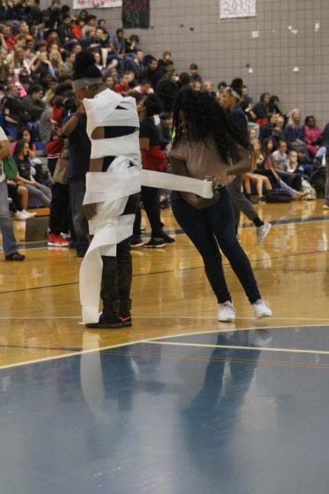 "Sophomore Erika Osei rolls toilet paper around sophomore Nuru Lewis as fast as she can during the mummy game. ""I was so nervous and hand shaking because the paper kept breaking and I wanted to win,"" said Osei."