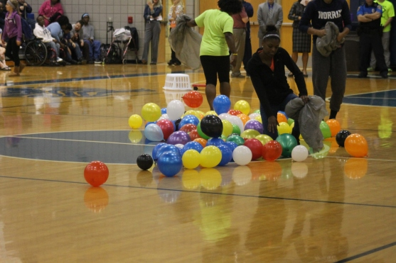 "Senior Jazmyn Jackson picks the balloons up after the balloon game at the gym. She was part of the staff because she is taking the sport and management class. ""We were supposed to be like the game Hungry Hippo,"" said Jackson."