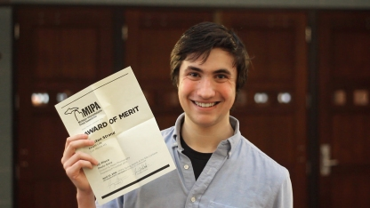 Senior Carsten Strand proudly shows his certificate for first place in the News Photo Story category. Strand received three other awards, as well as an honorable mention in the on-site writing contest in news writing. Photo Credit / Christian Baker