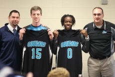 Senior basketball players Grant Mitchell and GK Wells-Lindsay pose with their high school and future college coaches. Both players have played three years of varsity basketball. Photo Credit / Paul Vallier
