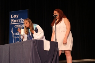 Senior class president Maddie Olech blows out the senior candle, passing it to the juniors. Photo Credit / Abby Farrer