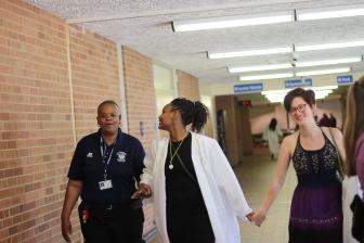 Alle Kistler Ellis and Shia'ann Lee SKip down the hallway while bugging Officer Watkins. Photo Credit / Frankie Stevens