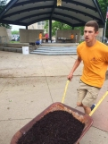 Junior Tony Dougherty runs with a wheelbarrow full of mulch back to the bed by City Hall. Students not only planted flowers but also laid down mulch and weeded the beds as well. Photo Credit / Rachel Zook
