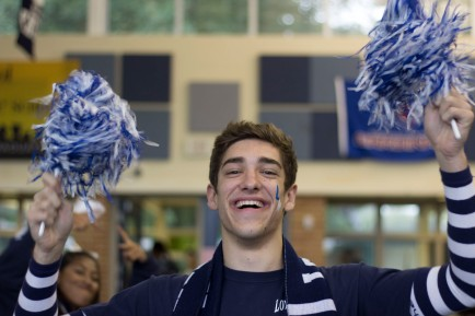 "FRIDAY: Senior Vaughn Taylor shows his school spirit with blue and white pom poms. ""I'm pumped for my last homecoming pep rally,"" said Taylor. Photo Credit / Hannah Pittman"