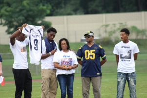 Friend, Damarquay Norman, presents to DQ's mother, Mabel Evans, the jersey once worn by Hunter. DQ's teammates signed the jersey for their friend, a four year football player. Photo Credit / Zachary Liddle