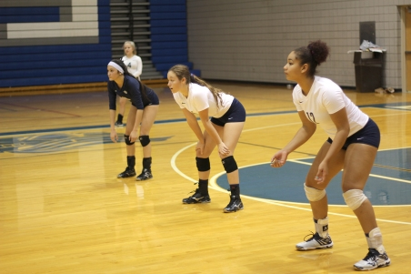 Senior Lizzie Ko, junior Abby Guimond, and senior Ashantai Hale-Sandifer prepare for the incoming serve. All are returning players from last season. Photo Credit / William Bowser