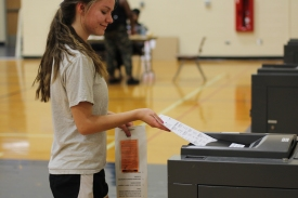 Junior Jenni Peterson puts her ballot into the tabulator to be counted. Photo Credit / Sidney Richardson