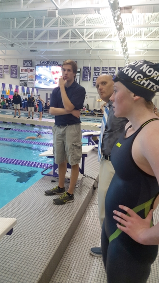 """Eva DeYoung, a junior at Loy Norrix focuses on her 400 freestyle relay at the S.M.A.C. conference. Coach Paul Mahar and Loy Norrix senior, Duncan Wallis help the relay team with their relay starts. """"My favorite part was the 400 freestyle relay when we were head to head with Battle Creek Central's relay and we pulled ahead to beat them,"""" DeYoung said. Photo Credit / Morgan McCue"""