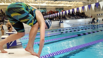 Delany Eller (left) a junior on the Loy Norrix swim team practices her track start for her upcoming race in the S.M.A.C. championships. This is her last chance to work out the little things that might delay her start during her race. Photo Credit / Morgan McCue