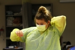 """Senior Grace Ritchie focuses on correct application and removal of personal protective equipment. Mrs Kuzmick watches Grace to make sure she knows how to put it on correctly and makes sure it's tied right. """"Putting on the PPE was difficult but all the practice helped a lot,"""" said Ritchie. Photo Credit / Meghan Lewis"""