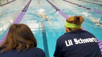 """Loy Norrix junior Madison Doonan (left) and sophomore Karli Little (right) are cheering for Isabella Valdez (center) during her 200 freestyle relay at the S.M.A.C. conference. """"We worked so hard this season and we got to see the results at conference,"""" said Little. Photo Credit / Morgan McCue"""