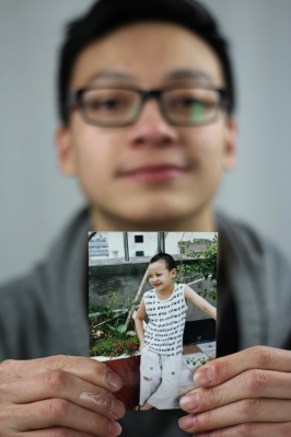 Zheng is photographed holding a childhood picture of himself during his time in China. Photo Credit / Christian Baker