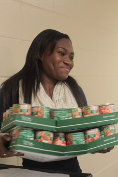 Senior Arika Hawkins happily helps collect all the food from different classes and helps carry it all to the food collection room. Photo Credit / Emma Whitehead