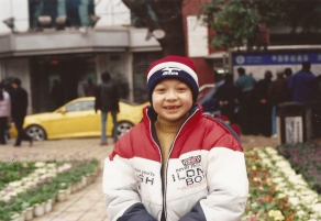 Zheng, dressed for cold weather, smiles, revealing his missing front teeth.