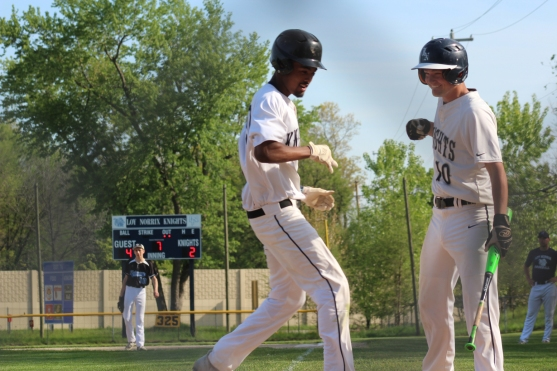 Senior Noel Cavey congratulates sophomore Yohaness Ademodi at home plate following Ademodi's two-run homer in the bottom of the 7th inning, to tie up the game. The Knights came out on top against the Kalamazoo Home School Cougars in extra innings for a win on senior night.