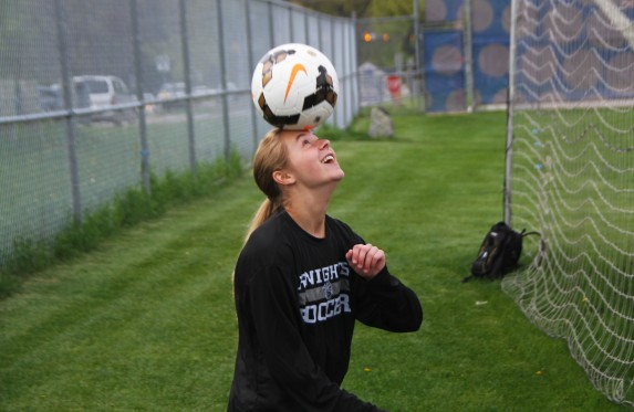 Junior Catie Stamper juggles the ball with her head in pregame warmups against Kalamazoo Central.