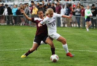 Junior forward Catie Stamper bounces off a Kalamazoo Central defender. Stamper scored one of the two goals scored by the Knights.