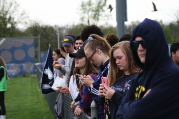 Loy Norrix students check their phones and conversate during a break in the game.