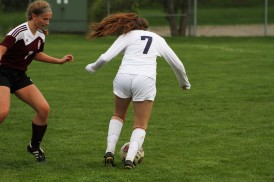 Freshman defender Emma Scheele crosses an opposing Kalamazoo Central defender. Scheele is one of seven freshmen on the varsity team.