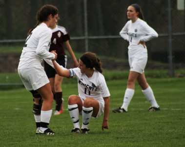 Freshman midfielder Anna Puca assists senior forward Maria Egloff back to her feet after getting fouled.