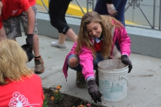 Senior Nora Hilgart-Griff smiles as she helps beautify downtown Kalamazoo. This annual tradition would not be possible without the help of so many volunteers like her. Photo Credit / Rachel Zook