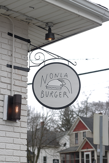 A small sign hangs in the front of the white brick building. The art is simplistic and adds to the modern twist of the retro diner. Photo Credit / Abigail Lindblade